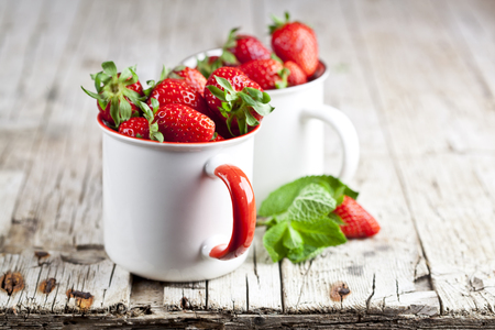 Organic red strawberries in two white ceramic cups and mint leaves on rustic wooden background. Healthy sweet food, vitamins and fruity concept.