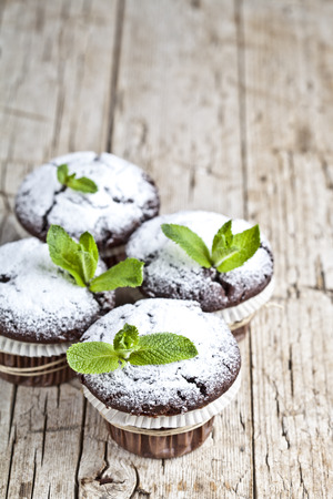 Fresh chocolate dark muffins with sugar powder and mint leaf on rustic wooden table background.