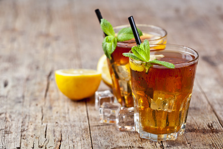 Traditional iced tea with lemon, mint leaves and ice cubes in two glasses on rustic wooden table background. With copy space. Archivio Fotografico