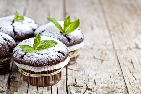 Fresh chocolate dark muffins with sugar powder and mint leaf on rustic wooden table background. With copy space. Foto de archivo