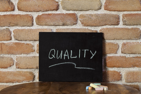 Chalk board with the word QUALITY drown by hand on wooden table on brick wall background. For business presentation. Stockfoto - 123164727