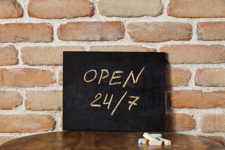 Black chalkboard with the phrase OPEN 24/7 drown by hand on wooden table on brick wall background. Presentation concept. Stockfoto - 123164744