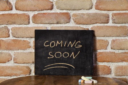 Black board with the phrase COMING SOON drown by hand on wooden table on brick wall background. Presentation concept.