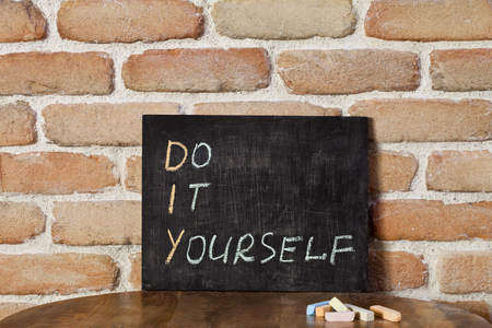 Black chalkboard with the phrase DO IT YOURSELF drown by hand on wooden table on brick wall background. Presentation concept. Stockfoto - 123164782