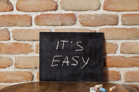 Black board with the phrase ITS EASY drown by hand on wooden table on brick wall background. Presentation concept.