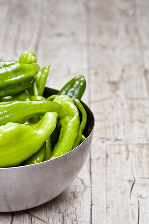 Fresh green raw peppers in metal bowl on rustic wooden table background. Vegan green food with copy space.