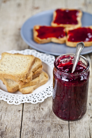 Homemade cherry jam and fresh toasted cereal bread slices plates closeup on rustic wooden table background. Sweet food for breakfast.