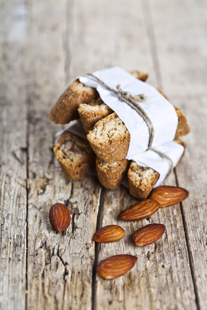 Fresh homemade Italian cookies cantuccini stackes and almond seeds on ructic wooden table background. Italian breakfast.