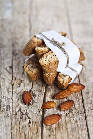 Frische hausgemachte italienische Kekse, Cantuccini-Stapel und Mandelkerne auf rustikalem Holztischhintergrund. Italienisches Frühstück.