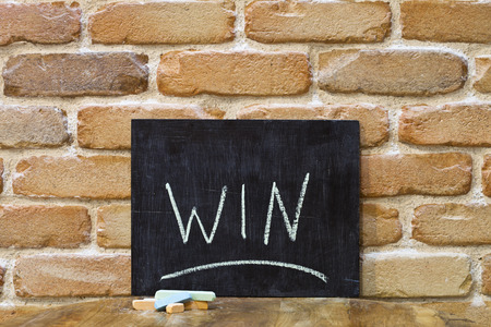 Chalk board with the word WIN drown by hand and chalks on wooden table on brick wall background. For busines presentation. Standard-Bild