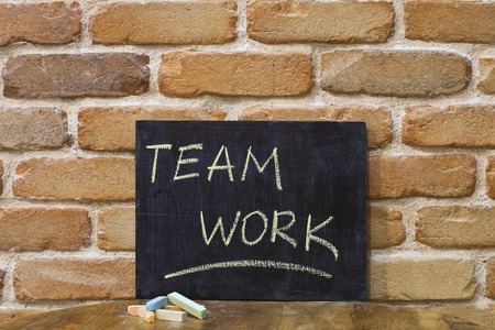 Chalk board with the word TEAMWORK drown by hand and chalks on wooden table on brick wall background. For busines presentation.