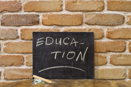 Chalk board with the word EDUCATION drown by hand and chalks on wooden table on brick wall background. For busines presentation.