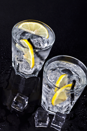 Glasses of fresh cold carbonated water with ice cubes and lemon slices. Soda water on black background.