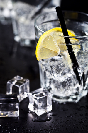 Glasses with fresh cold carbonated water with lemon slices and ice cubes closeup. Soda water on black background. Фото со стока