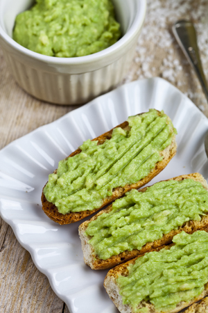 Fresh crostini with avocado guacamole on white plate closeup on rustic wooden table. Diet breakfast. Delicious and healthy plant-based food.