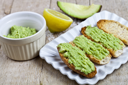 Crostini with avocado guacamole on white plate closeup on rustic wooden table. Diet breakfast. Delicious and healthy plant-based food. Stock Photo