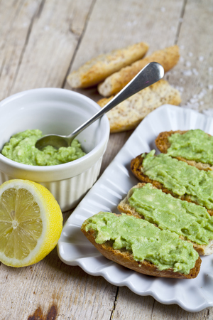 Toasts with avocado guacamole on white plate closeup on rustic wooden table. Diet breakfast. Delicious and healthy plant-based food. Stock Photo
