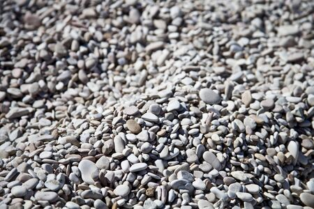 Abstract background with grey and white peable stones on Adriatic beach.