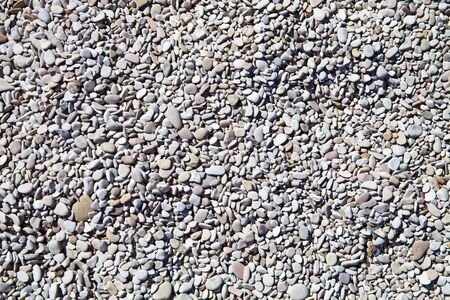Abstract background with grey and white peable stones on Adriatic beach. Top view.