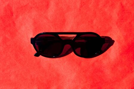 Fashionabls black sunglasses with shadow on red background. Top view.