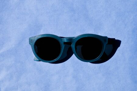 Stylish sunglasses with shadow on blue background. Top view.