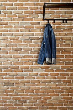Modern hallway loft interior with denim coat on hanger against brick wall. With copy space.