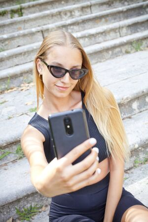 Attractive happy young woman taking selfie on the ancient town stairs.