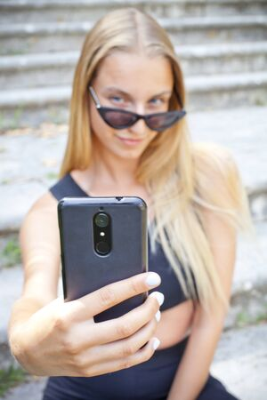 Attractive young woman in sunglasses taking selfie on the ancient town stairs.