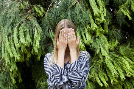 Beautiful young woman wearing elegant clothes hiding her face standing in the forest against fir trees. Stockfoto