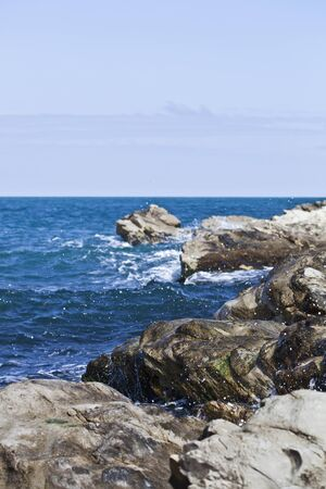 Seascape with blue sea water, stones and rocks on Adriatic sea coast.