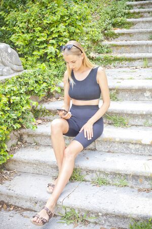 Attractive young woman with smartphone on the ancient town stairs.