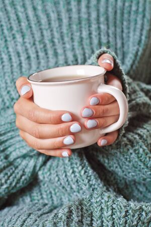 Female hands holding hot cup of coffee or tea. Warm gfeen sweater and ceramic cup of tea.