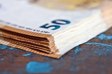 Pile of fifty euro banknotes. Currency bank notes stacked on rustic wooden table background closeup.