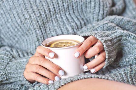 Mains féminines tenant une tasse de thé chaud au citron le matin. Jeune femme relaxante tasse de thé à portée de main. Bon thé du matin ou ayez un concept de message de bonne journée.