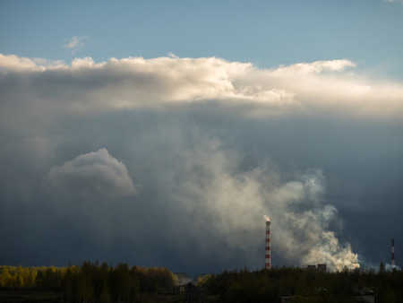 Dense clouds of smoke or a pair of two pipes against a cloud background. The railway with a train going into the distance. The concept of ecology, pollution of the environment.