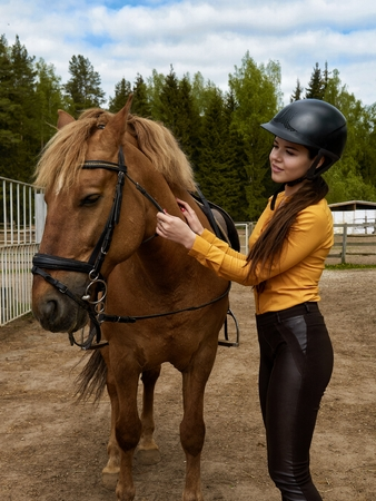 Young cheerful girl equestrian hugging her favorite red horse. Vertical image