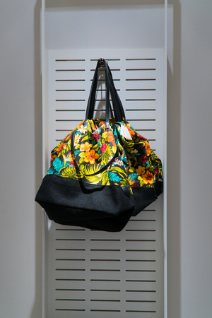 clothing store: A colored bag is sold in the store. A stylish bag hangs on the wall in the store. Stock Photo