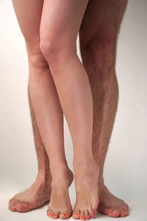 adult sex: Smooth female and hairy male feet on a light background. Sexual overtones. Stock Photo