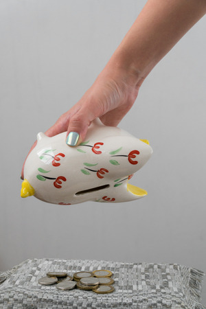 The girl is emptying the piggy bank. Piggy bank in the form of a painted pig. A handful of coins.