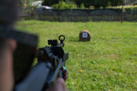 여자가 공압 총에서 표적을 쏘고. 어깨 뒤에서 볼 수 있습니다.