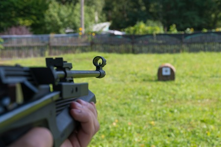 A man shoots a target from a pneumatic gun. A view from behind the shoulder.