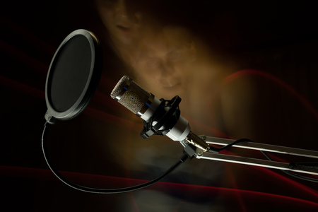 Professional condenser studio microphone on the black background and freezelight and faces. Stock Photo