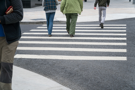 People cross the road on a pedestrian crossing.