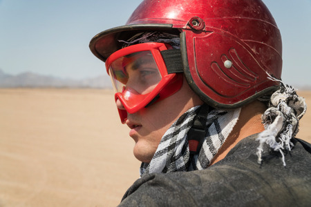 Young guy during desert excursion by quad - Man in helmet and adventure clothes in exotic scenarios - Concept of activity holiday, freedom and adventure. Imagens