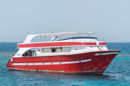 A motor yacht under way on tropical sea.