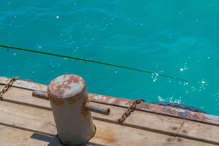 Old, rusty bollard with metal chain on pier with water