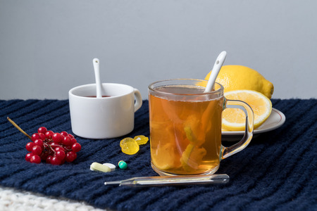 Still life of tea with lemon, tablets and thermometer, jam and berries. The concept of treating colds.