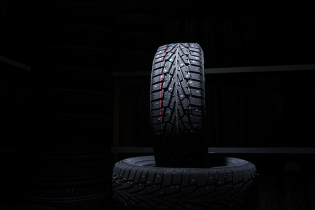 Winter tire on the background of racks with tires. Stock Photo