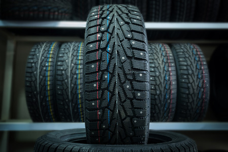 Winter tire on the background of racks with tires. Foto de archivo