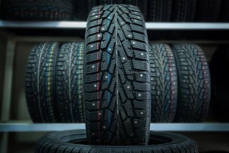 Pneu d'hiver sur le fond des grilles avec des pneus. Banque d'images - 90184523